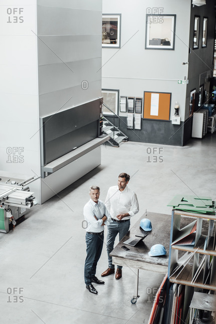 Male colleagues standing by table in manufacturing industry
