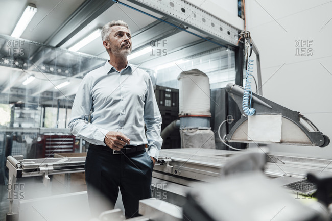 Male engineer looking away while standing by manufacturing equipment in factory