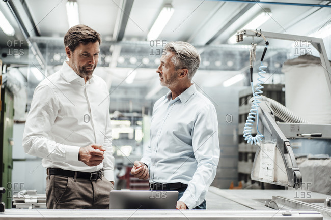 Mature male engineers discussing over laptop in manufacturing industry