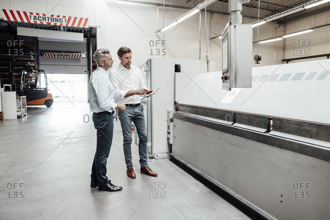 Male engineers discussing over digital tablet while standing by manufacturing equipment in industry