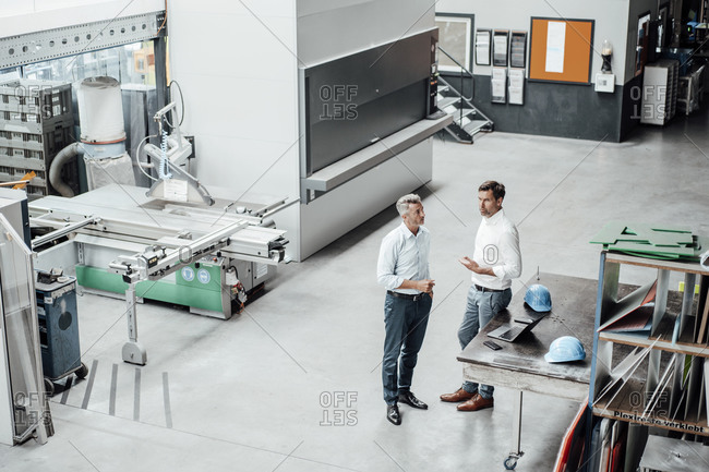 Mature businessmen discussing while standing in manufacturing industry