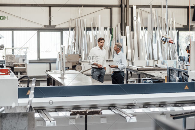 Male mature engineers discussing while standing in factory