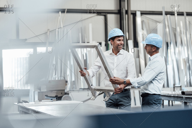 Male engineers discussing over metallic frame in industry