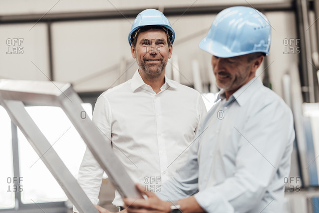 Male engineer smiling while colleague holding metallic frame in industry