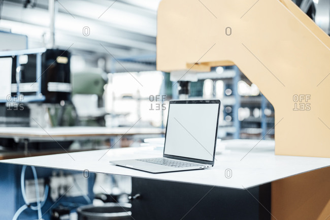 Laptop with blank screen on table in industry