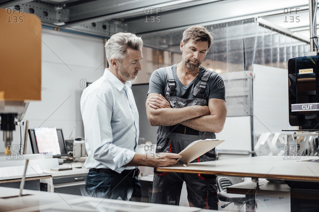Mature manager discussing with worker over document while standing in factory