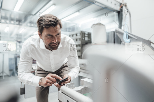 Male engineer using smart phone while examining manufacturing equipment in industry