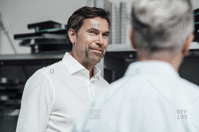 Smiling colleague discussing with manager while standing in manufacturing factory