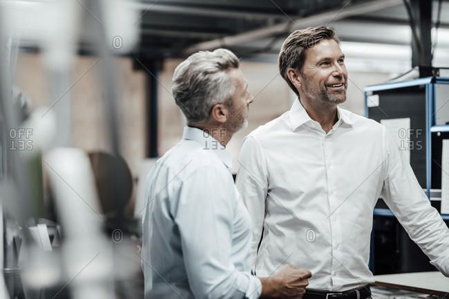Male colleague discussing with smiling manager in manufacturing industry
