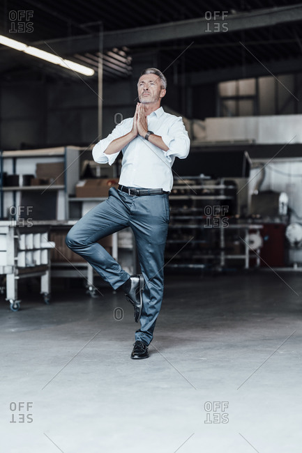 Male engineer with hands clasped standing on one leg in manufacturing industry