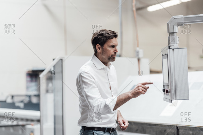 Mature engineer pointing while looking at equipment in manufacturing industry