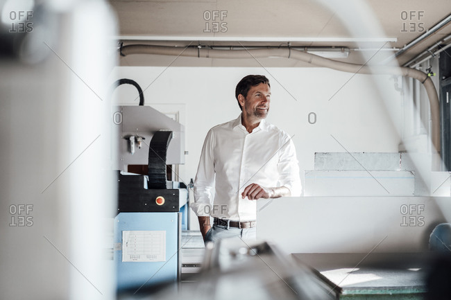 Smiling manager with hand in pocket looking away while standing by manufacturing equipment in industry
