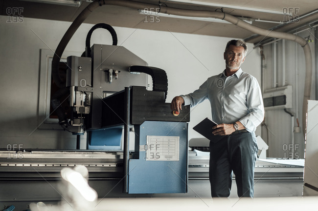 Male engineer with digital tablet standing by manufacturing equipment in factory