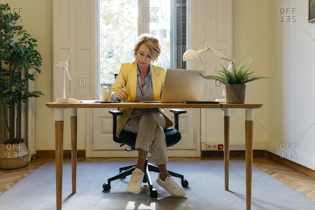 Female architect sitting with laptop while working at office