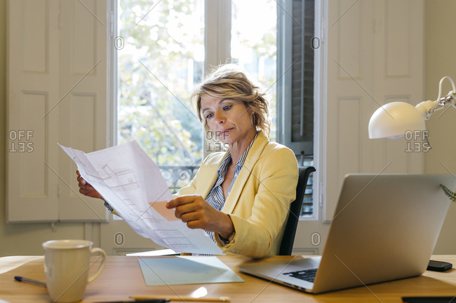 Female architect examining blueprint while sitting on chair in office