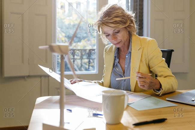 Female architect analyzing blueprint while sitting in office