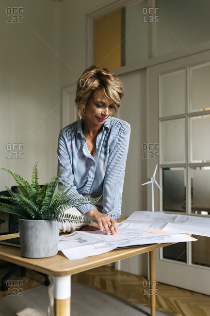 Female architect analyzing blueprint while sitting on desk in office