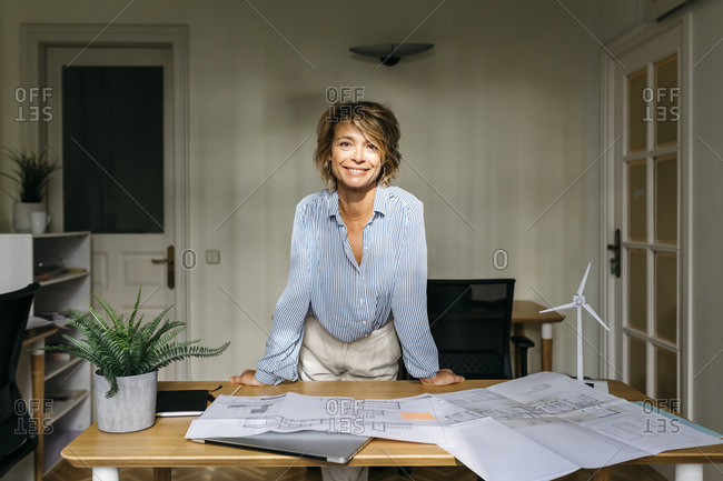 Smiling female architect leaning on desk while standing in office