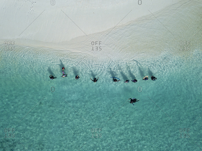 Women in traditional Muslim clothes at tropical beach- aerial view