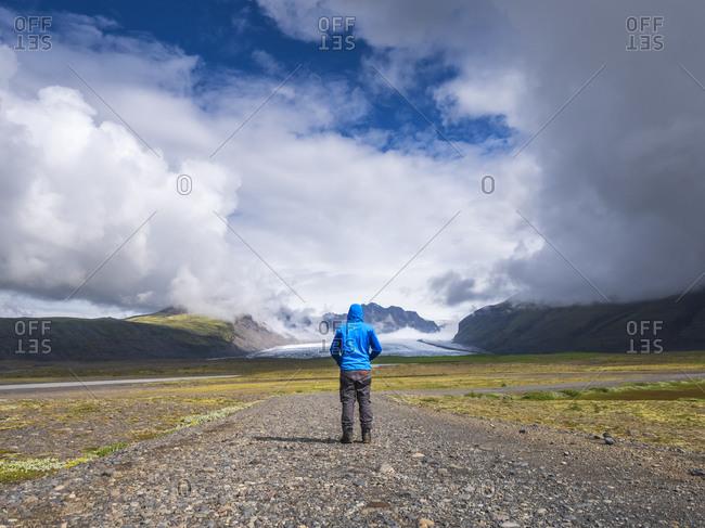 Man standing on dirt road against dramatic sky at Svinafellsjokull- Iceland