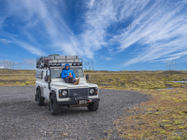 Happy mid adult man relaxing on hood of off-road vehicle during road trip at Jokulsarlon- Iceland