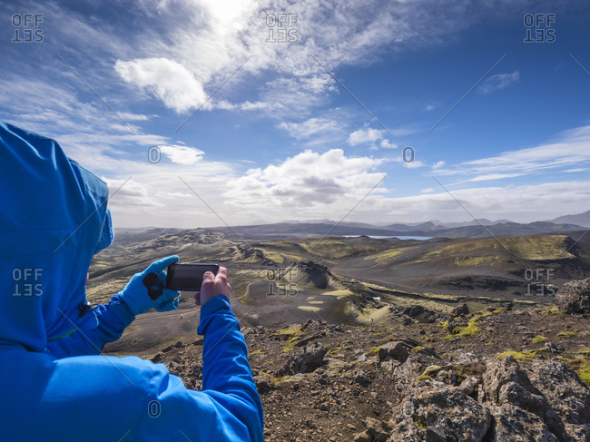 Man taking picture of landscape on smart phone during sunny day- Lakagigar- Iceland