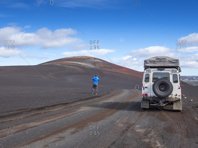 Male tourist standing on dirt road by off road vehicle against blue sky- Lakagigar- Iceland