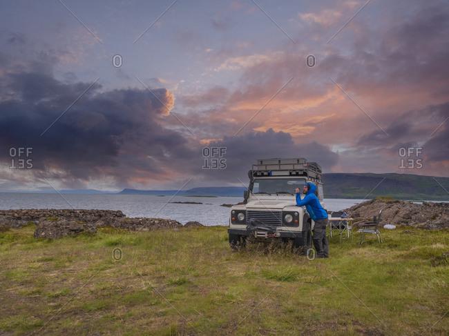 Man leaning on off-road car parked on grassy Icelandic coastline at cloudy dusk