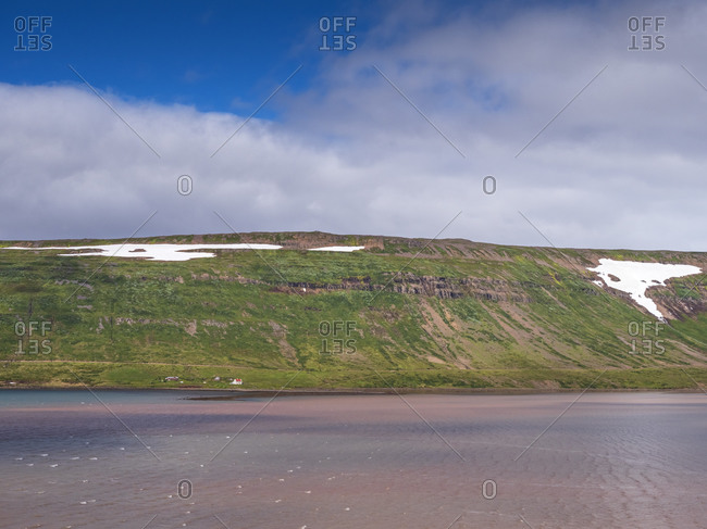 Secluded farm at foot of coastal hill in Westfjords