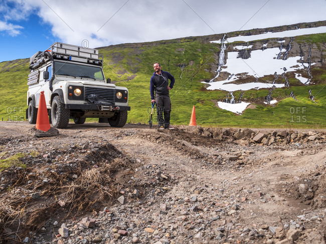Man leaning on shovel in front of pot hole in middle of dirt road leading to Drangajokull