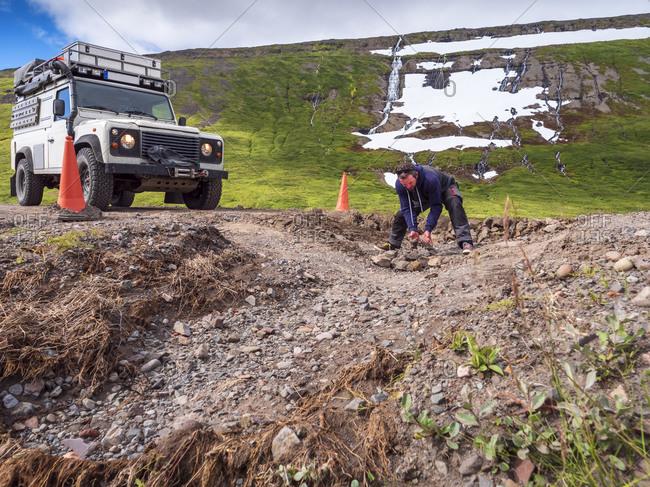 Man repairing pot hole in middle of dirt road leading to Drangajokull