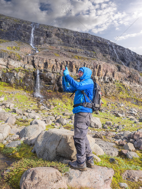 Male hiker taking smart phone photos in front of remote waterfall