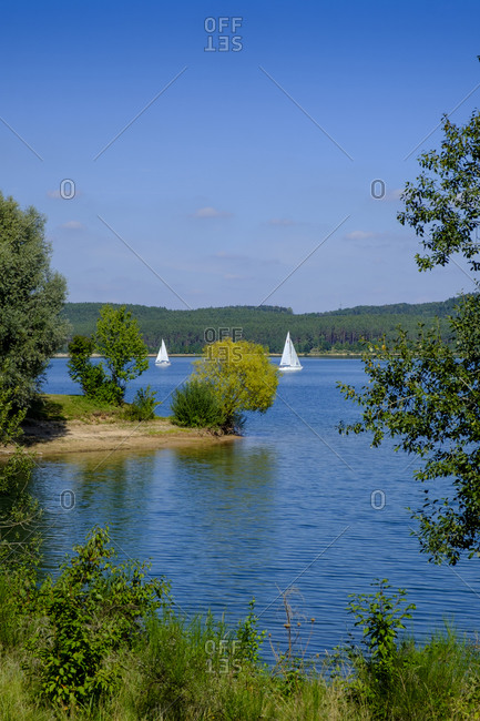 Sailboats on Brombachsee lake with trees in foreground