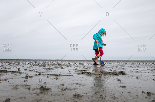 Girl playing in mud flat against sky at Lower Saxon Wadden Sea National Park- Germany