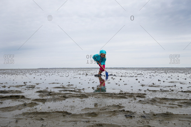 Girl playing in mud flat with shovel against sky at Lower Saxon Wadden Sea National Park- Germany