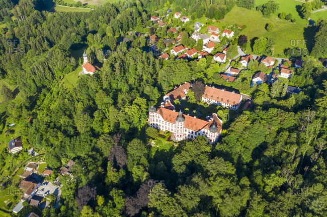 Germany- Bavaria- Eurasburg- Drone view ofEurasburg Castle surrounded by green grove