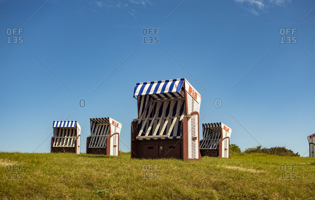 Hooded beach chairs standing on grass