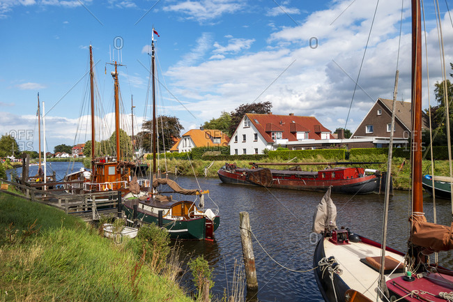 Germany- Lower Saxony- Wittmund- Sailboats moored along bank of Harle river