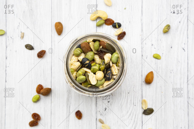 Jar of raisins- peanuts- cashew nuts- almonds- soybeans- sunflower seeds and pumpkin seeds on wooden background