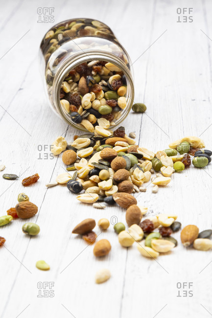 Jar of raisins- peanuts- cashew nuts- almonds- soybeans- sunflower seeds and pumpkin seeds spilled on wooden background