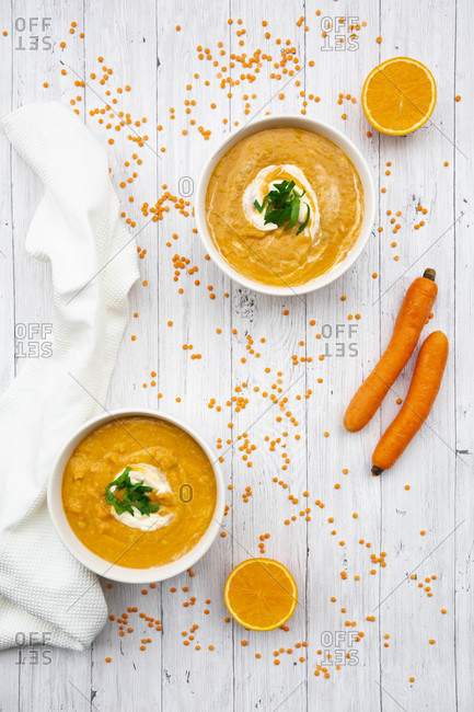 Two bowls of vegetarian lentil soup with carrots- orange juice- creme fraiche and parsley
