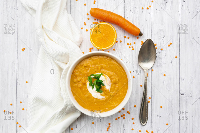 Bowl of vegetarian lentil soup with carrots- orange juice- creme fraiche and parsley