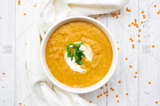 Bowl of vegetarian lentil soup with carrots- orange juice- cremefraicheand parsley