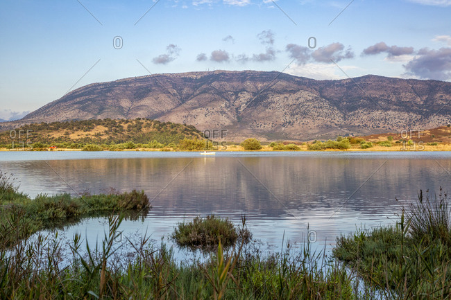 Shore of Lake Butrint in Butrint National Park with mountain in background