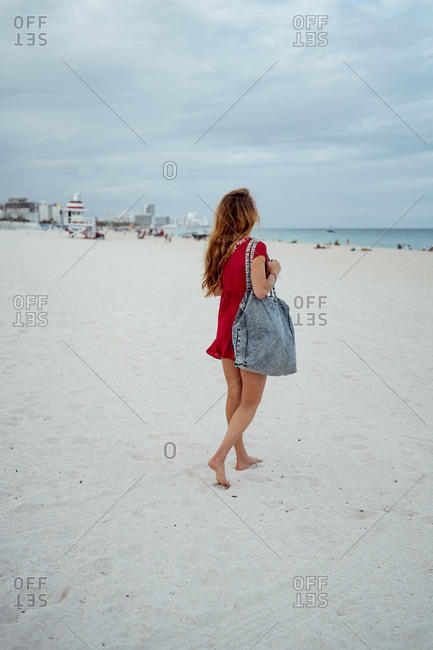 Young woman looking at sea while walking on sand against sky