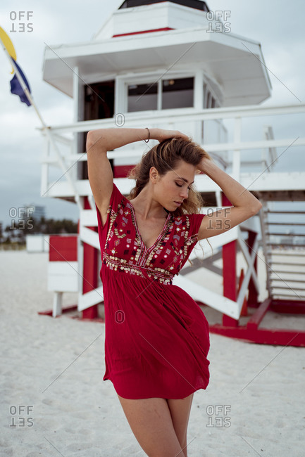 Young woman wearing red dress with hand in hair standing on sand at beach