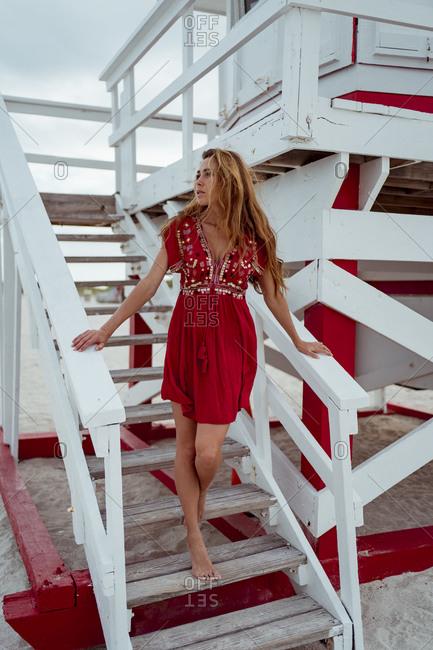 Brown hair woman looking away while walking downward on steps at beach