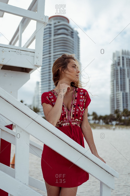 Beautiful woman wearing red dress leaning on wooden structure of lifeguard hut at beach