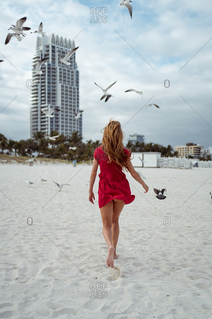 Seagull flying while woman walking on sand against sky at beach