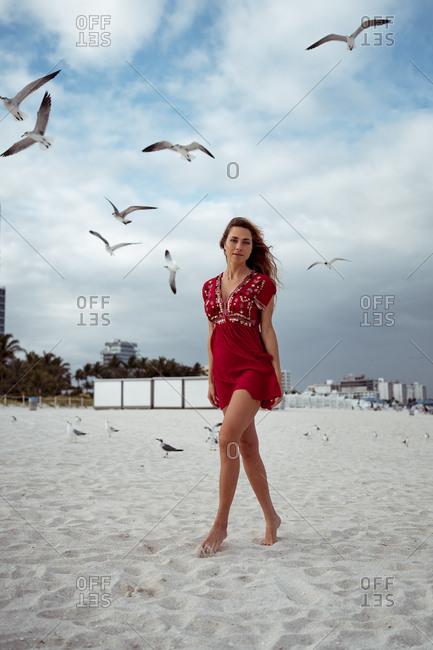 Beautiful woman standing while seagull flying against sky at beach